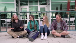 Group of Students Having Fun Sitting and Laughing Together Outdoors in Winter on University Campus