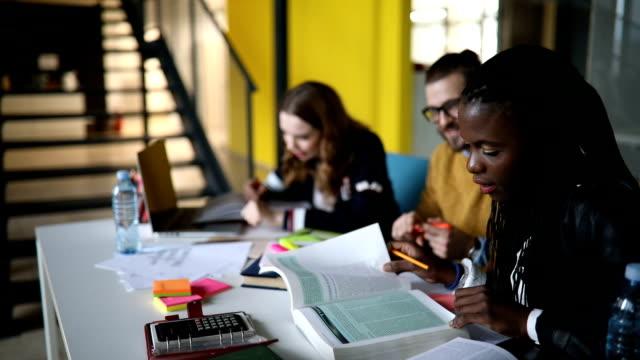 stockvideo's en b-roll-footage met groep studenten in bibliotheek samen te werken aan het project - testuitslag