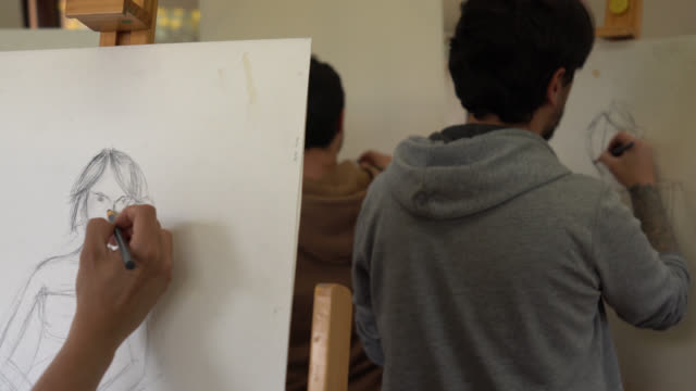 group of students painting with charcoal while looking at a female model at the front of the class - art class stock videos & royalty-free footage