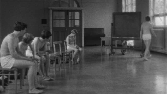 1976 B/W WS Group of students stripped to their underwear, one rises and walks behind a dividing screen / Liverpool, Merseyside, England