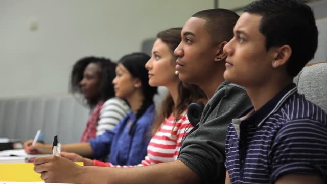 ms r/f zi group of students taking notes in lecture hall / london, england - lecture hall bildbanksvideor och videomaterial från bakom kulisserna