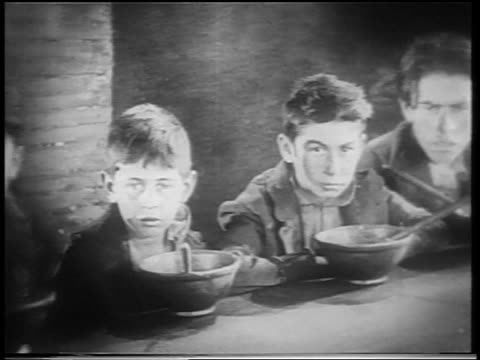 b/w 1922 pan group of sullen orphan boys sitting at long table with bowls staring at camera / feature - orphan stock videos & royalty-free footage