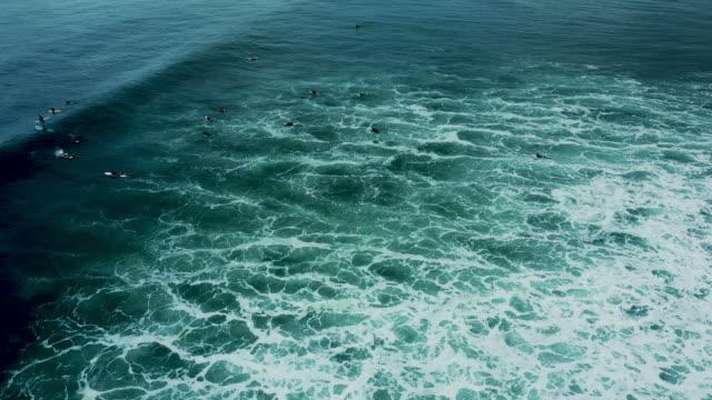 波を漕ぐサーファーのグループがバリでうねりを - 波点の映像素材/bロール