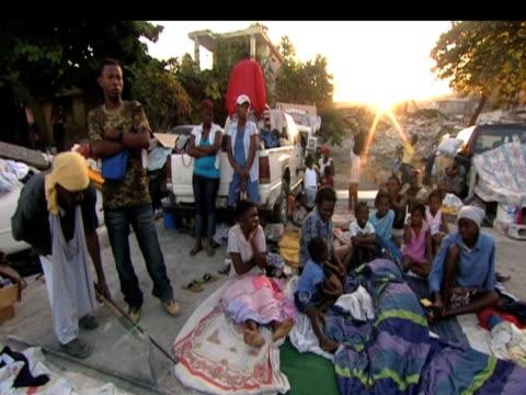 vídeos de stock e filmes b-roll de group of survivors wait for help on roadside following devastating earthquake haiti 19 january 2010 - hispaniola
