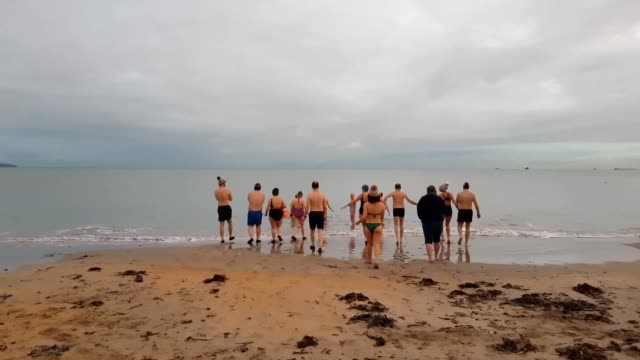 a group of swimmers gathered at the beach at helen's bay co down at sunrise to greet the winter solstice from the water - solstice stock videos & royalty-free footage