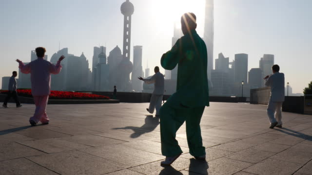 CU Group of Tai Chi practitioners exercising in front of Pudong skyline at sunrise