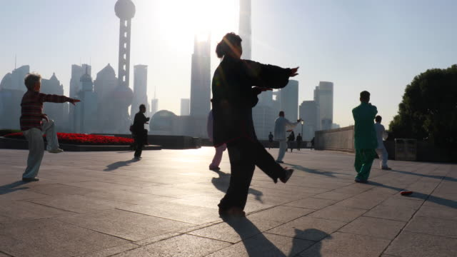 stockvideo's en b-roll-footage met ms group of tai chi practitioners exercising in front of pudong skyline at sunrise - chinese culture