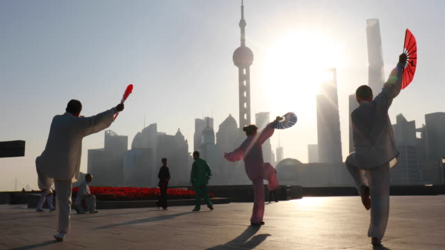 MS Group of Tai Chi practitioners exercising with Chinese fans in front of Pudong skyline at sunrise