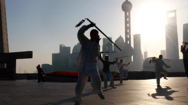 vídeos de stock e filmes b-roll de cu group of tai chi practitioners with swords exercising in front of pudong skyline at sunrise - artes marciais