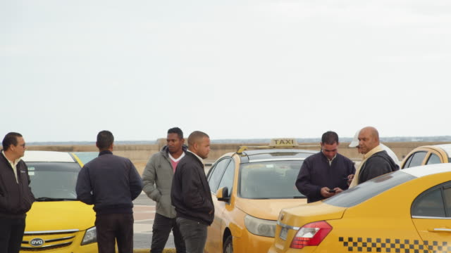 a group of taxi drivers waiting for passengers in havana, cuba on a cold, cloudy day - jacket stock videos & royalty-free footage