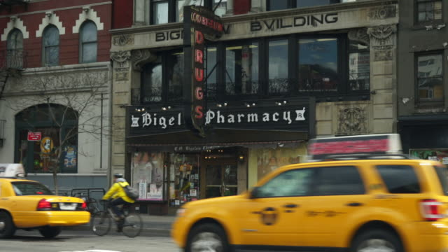 A group of taxi's drive by a old style Pharmacy on 414 6th Ave in New York City