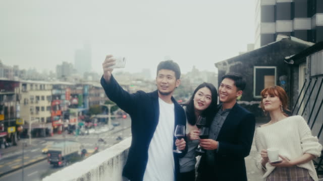 Group of team members taking a selfie at after work party (slow motion)