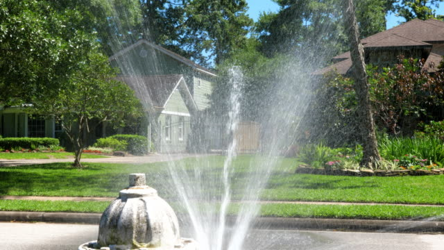 MS Group of teen friends running through spray from fire hydrant on summer afternoon