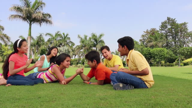 group of teenage boys and girls playing arm wrestling in the park, delhi, india - arm wrestling stock videos & royalty-free footage