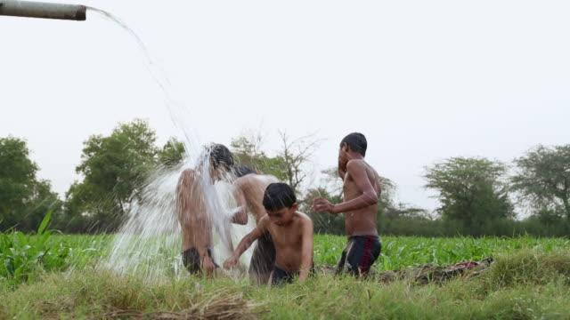 vídeos y material grabado en eventos de stock de group of teenage boys bathing in the farm, haryana, india - sin camisa