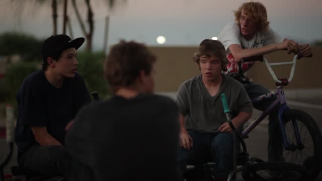 Group of teenage boys with their BMX bikes hanging out in parking lot