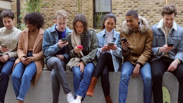 group of teenage friend focused on their own smartphone texting on social media - sharing stock videos & royalty-free footage