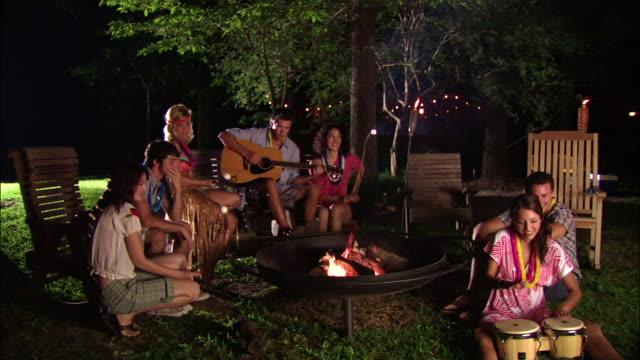 vídeos de stock, filmes e b-roll de ws group of teenage girls and young men roasting marshmallows around campfire, playing acoustic guitar and bongos / mabank, texas, usa - tocha tiki
