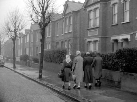 a group of teenage girls wearing raincoats and scarves walk along a typical suburban street 1957 - bbc archive stock-videos und b-roll-filmmaterial