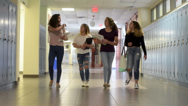 vídeos de stock, filmes e b-roll de group of teenaged girls walking down school hallway. - corpo inteiro