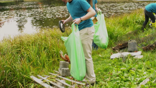 ms shaky group of teenagers cleaning lake shore from garbage, dorset, vermont, usa - wackelaufnahme stock-videos und b-roll-filmmaterial