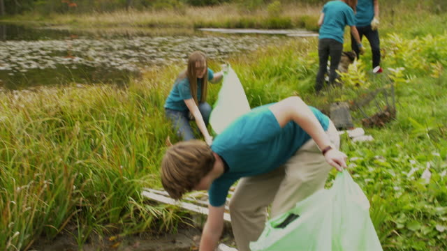 ms tu td group of teenagers cleaning lake shore from garbage, dorset, vermont, usa - teenagers only bildbanksvideor och videomaterial från bakom kulisserna