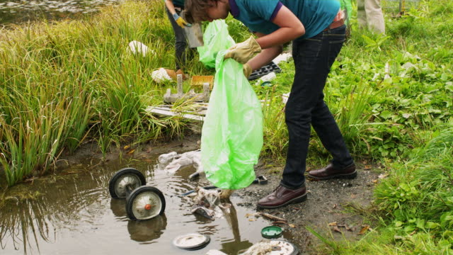ms shaky group of teenagers cleaning lake shore from garbage, dorset, vermont, usa - water pollution stock videos & royalty-free footage