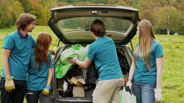 ms group of teenagers loading garbage bags into car trunk, standing on field, dorset, vermont, usa - loading stock videos & royalty-free footage