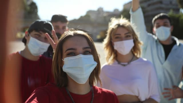 vídeos de stock e filmes b-roll de group of teenagers posing showing their protective face masks - cultura jovem