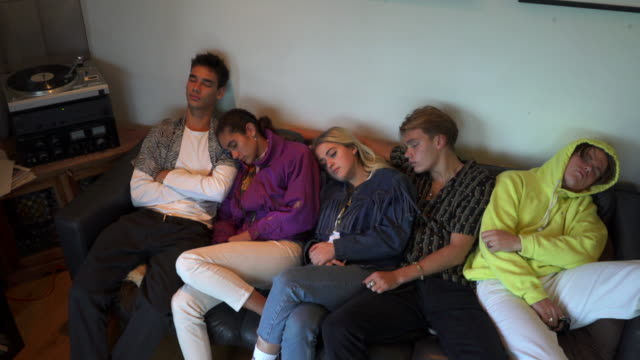 vídeos de stock, filmes e b-roll de a group of teenagers sleeping on a sofa listening to vinyl. - jaqueta jeans