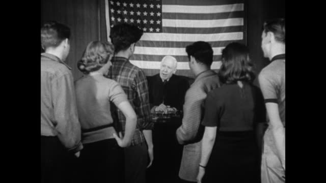 group of teenagers standing in front of a judge sitting behind a large American flag / judge reprimanding teens for drug possession and selling...