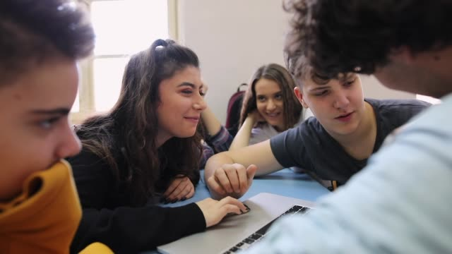 Groupe d'adolescents parlant et souriant pendant qu'ils utilisent l'ordinateur portatif