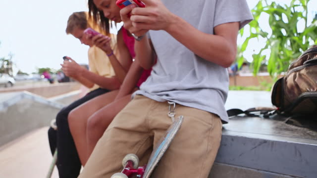 ms tu group of teenagers texting or using their cell phones at skatepark / santa fe, new mexico, united states - teenage boys stock videos & royalty-free footage
