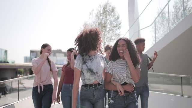 vídeos de stock e filmes b-roll de group of teenagers walking through city - 14 15 anos