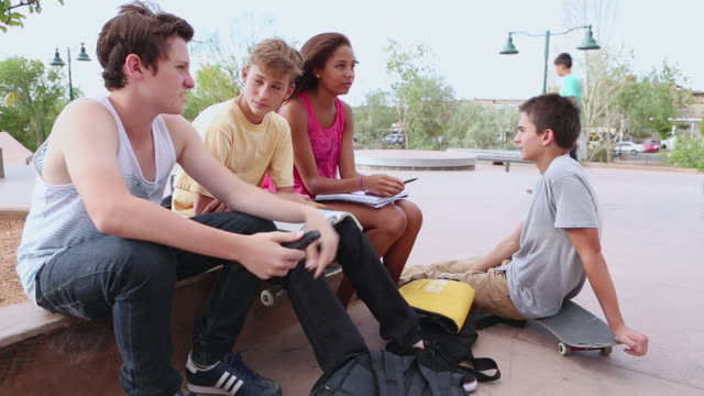 MS TU Group of teenagers working on homework at skatepark / Santa Fe, New Mexico, United States