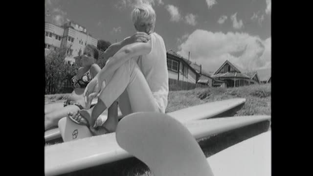 vídeos y material grabado en eventos de stock de group of teenagers youths sits on grass on surfboards young woman sitting on board in bikini / rear shot anon youths sitting on malibu style... - surf en longobard