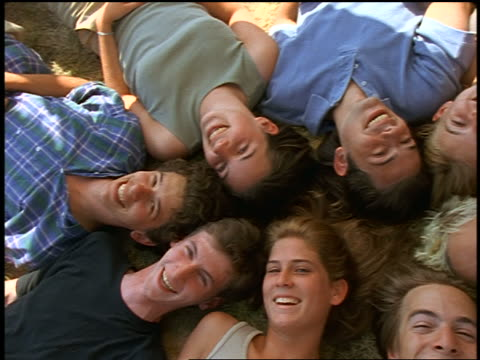 overhead portrait group of teens lying together on ground smiling at camera / montana - teenagers only stock videos & royalty-free footage