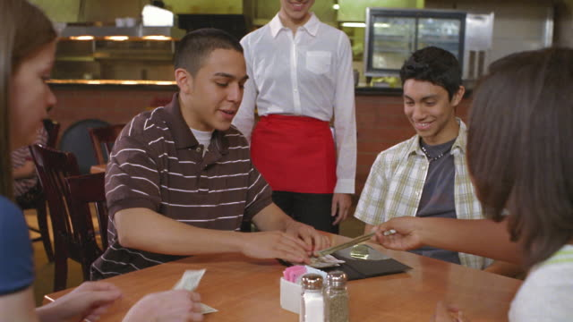 ms group of teens paying for meal in restaurant and giving money to waitress / san antonio, texas, usa - financial bill stock videos & royalty-free footage
