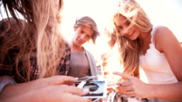 Group of teens sharing instant photographs