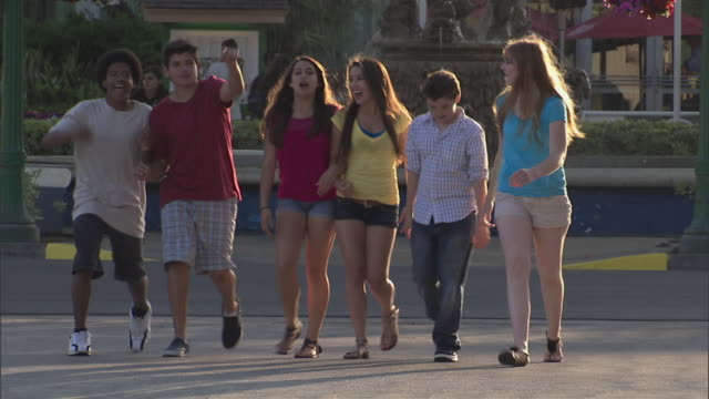 vídeos de stock, filmes e b-roll de group of teens walking, talking, laughing as they enter knott's berry farm theme park, pan faces - 2010