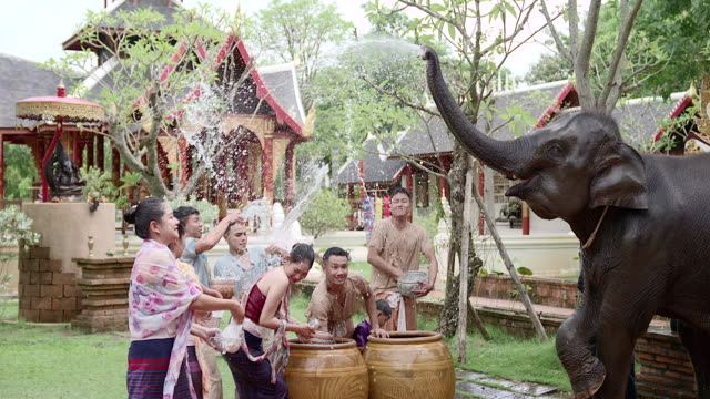 vídeos de stock e filmes b-roll de group of thai and laos boys and girls splashing water during festival songkran festival - 12 15 meses