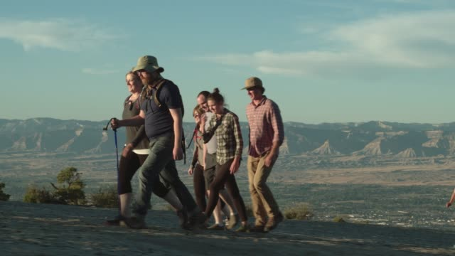 A Group of Thirty-Something People Hike Together in the Desert of the Colorado National Monument Over Grand Junction, Colorado Overlooking the Bookcliffs at Sunset