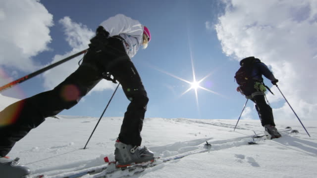 ms pan group of three mountain climbers trekking on snow and ice covered mountain in austrian alps at morning sunlight / stubai glacier, tirol, austria  - moving up stock-videos und b-roll-filmmaterial