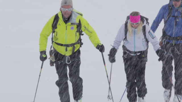 ms tu pan group of three mountain climbers trekking on snow and ice covered mountain in austrian alps at snow storm / stubai glacier, tirol, austria  - スキーウェア点の映像素材/bロール