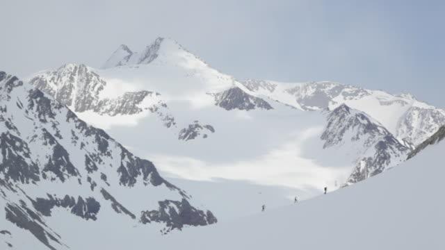 ws pan group of three mountain climbers trekking on snow covered mountain in austrian alps / stubai glacier, tirol, austria  - austria stock videos & royalty-free footage