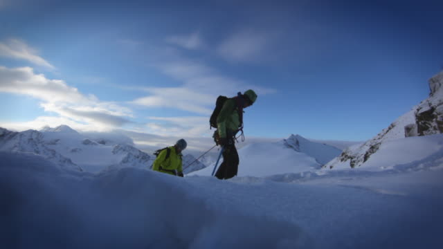 a group of three mountain climbers trekking up a snow covered mountain in the austrian alps. - beweglichkeit stock-videos und b-roll-filmmaterial
