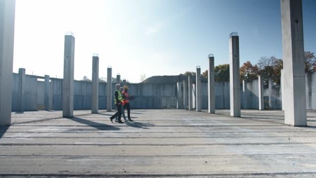 gruppe von drei multiethnischen bauarbeitern, die auf einer leeren baustelle herumlaufen - architekt stock-videos und b-roll-filmmaterial