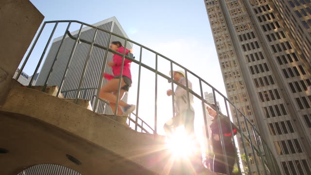 a group of three women running together in a urban area on a sunny day. - moving up stock videos & royalty-free footage