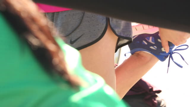 A group of three women stretching before a run together outside in a urban area.