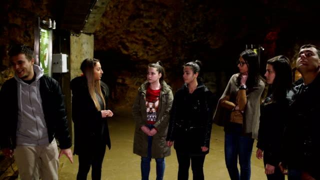 vídeos y material grabado en eventos de stock de grupo de turistas en la cueva - geología